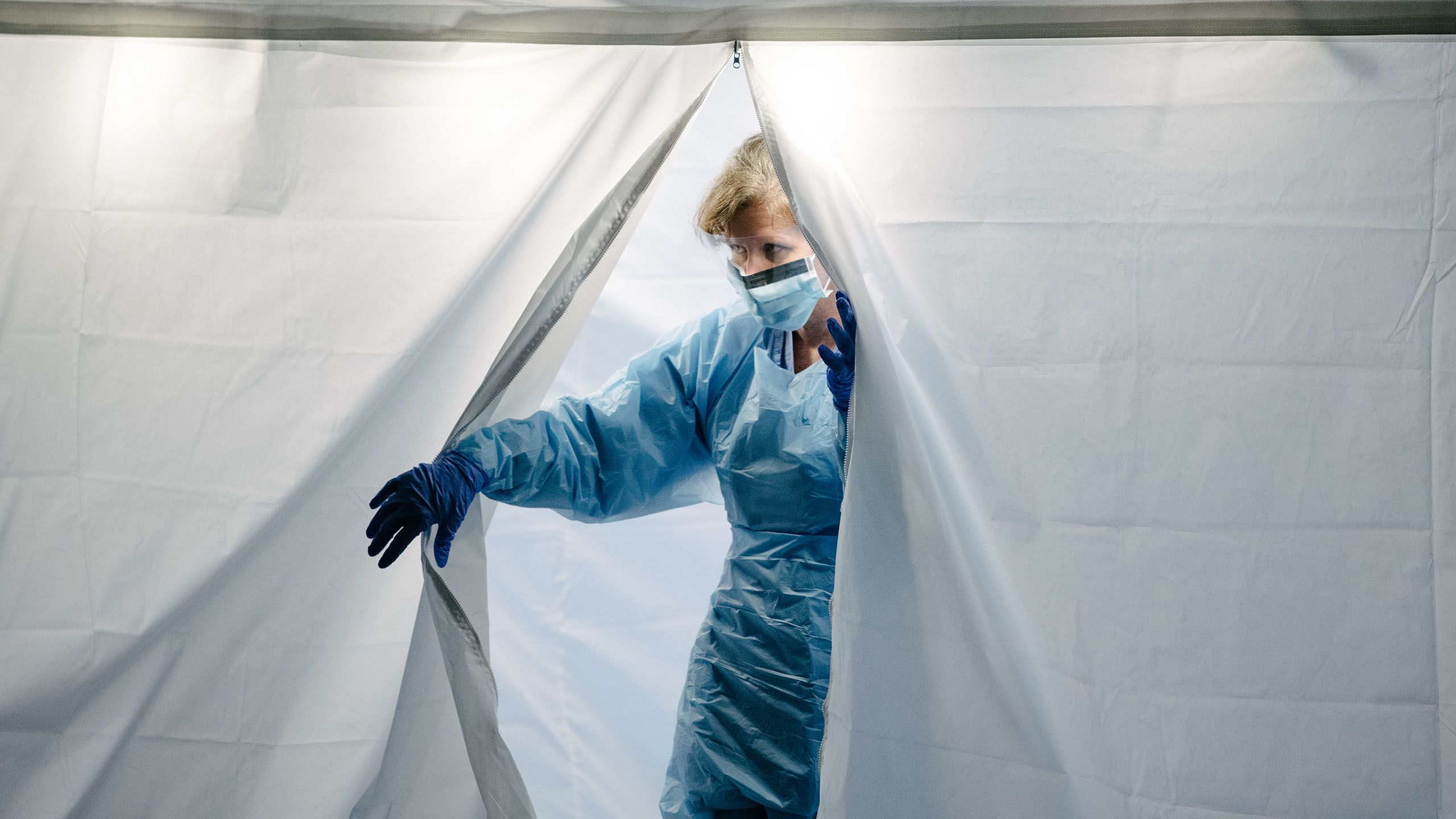 UW Medicine COVID-19 tester exits tent wearing personal protective equipment